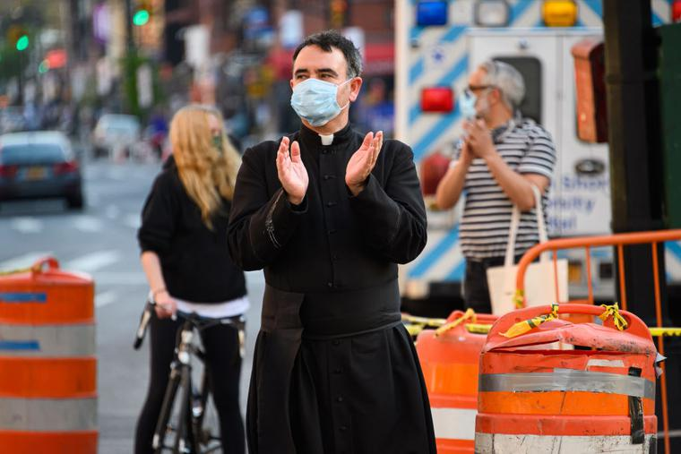 A priest applauds to show his gratitude to medical staff and essential workers on the front lines of the coronavirus pandemic outside Lenox Health Greenwich Village on May 15, 2020 in New York City.