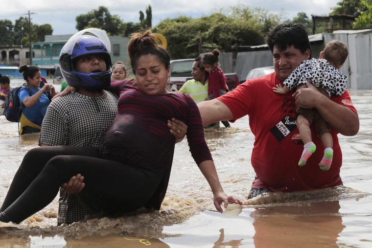 A pregnant woman is carried out of an area flooded by water brought by Hurricane Eta in Planeta, Honduras on Nov. 5, 2020.