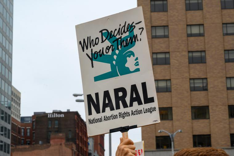 An pro-abortion activist carrying a NARAL (National Abortion Rights Action League) sign at a rally.