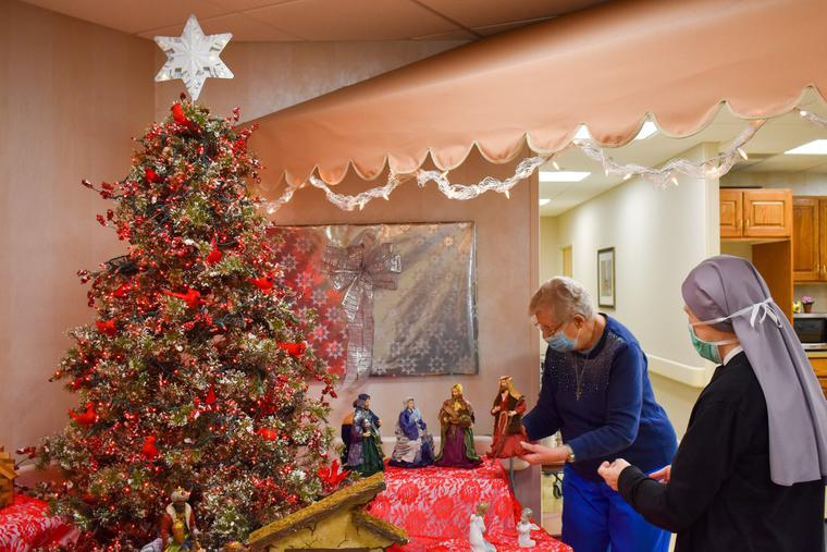 Resident Betsy Balmes of the Mullen Home in Denver and Sister Carolyn Martin, of the Little Sisters of the Poor, who is a nurse, administrator and vocations outreach manager at the Mullen Home, work together on the Christmas display in the first floor coffee shop.