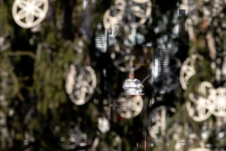 Pope Francis, seen through the Vatican's Christmas tree, delivers an Angelus address.