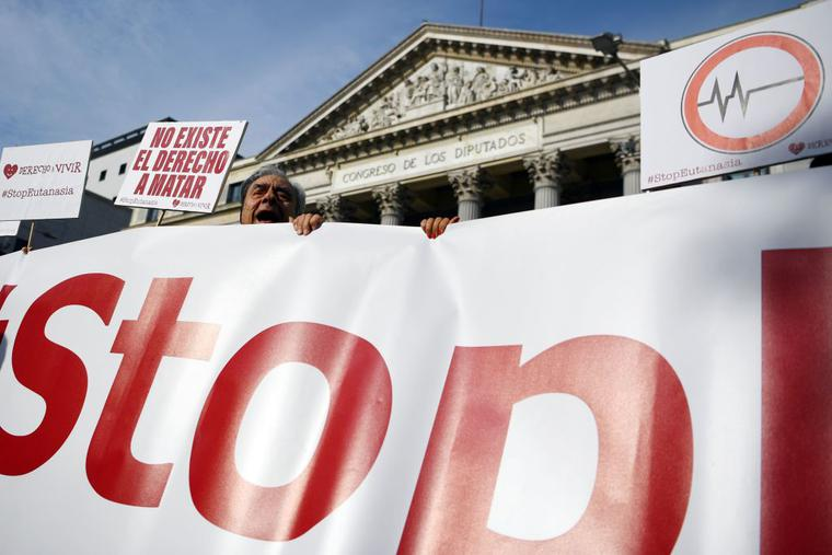 """A man holds a sign reading in Spanish """"There is no right to kill"""" during a demonstration against euthanasia called by """"Derecho a Vivir"""" (Right to live) group in front of the Parliament in Madrid."""