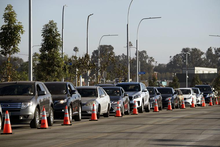Vehicles wait in line to receive groceries during a holiday mobile food distribution from the Los Angeles Regional Food Bank on Dec. 22, 2020, in Inglewood, California. The food bank has distributed 145 million pounds of food since the COVID-19 pandemic started.