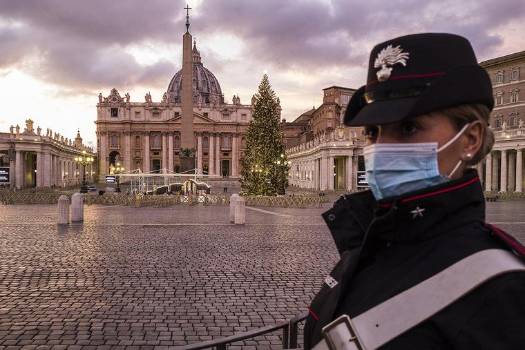 A carabiniere stands watch at an empty St. Peter's Square during the first evening of Italy's nationwide lockdown on Christmas Eve, Dec. 24, 2020.