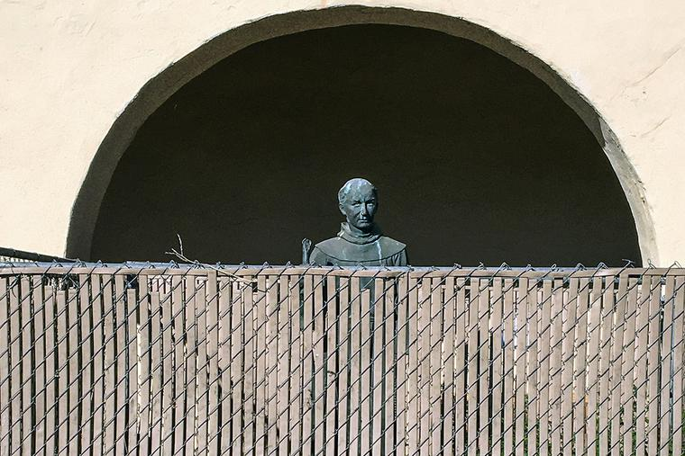 A bronze statue of St. Junípero Serra, located at the entrance to the Old Mission Santa Inés, is surrounded by a chain link fence to protect it on Nov. 2, 2020, in Solvang, California.