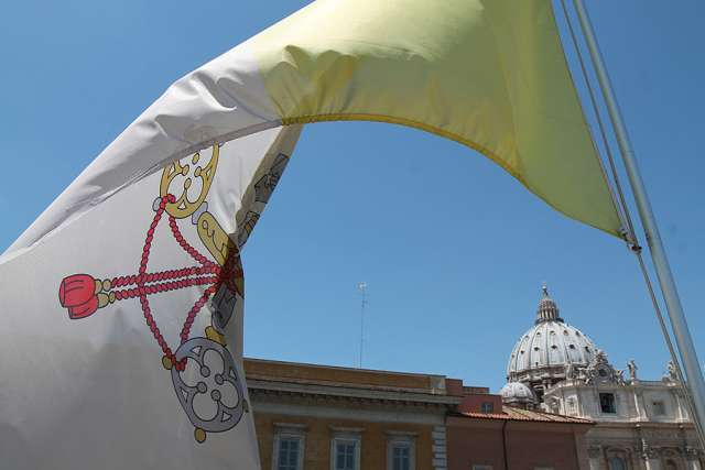 The Vatican flag waves over the dome of St. Peter's Basilica.