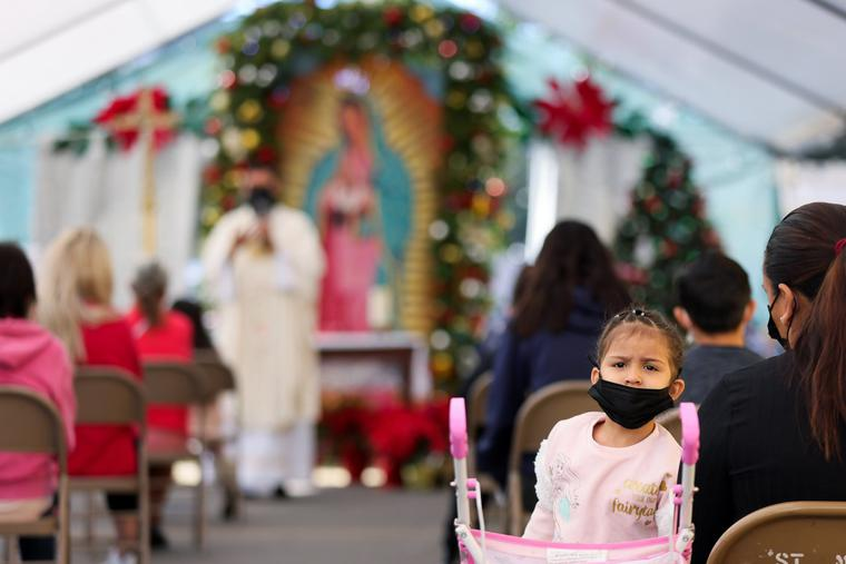A girl wears a face covering as Father Rafael Saiz holds Christmas Mass outdoors at St. Mary's Catholic Church on Dec. 25, 2020, in Los Angeles.