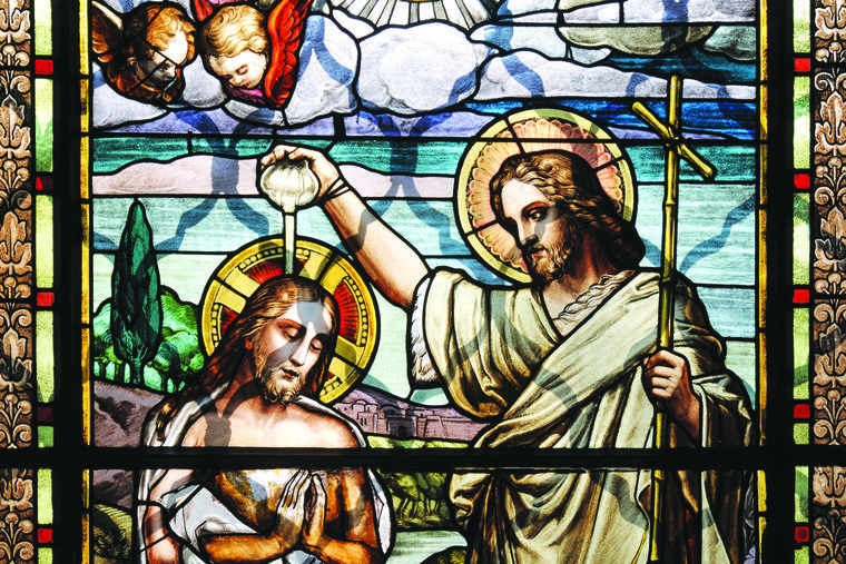 Jesus Christ is shown being baptized by St. John the Baptist in an old stained-glass window.