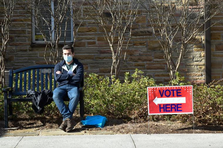 A man sits next to a 'vote' sign outside on Jan. 5 in Atlanta during the Georgia Senate runoff elections.