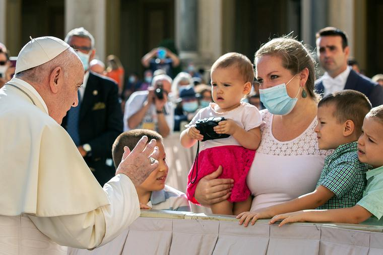 Pope Francis greets a family at his second public general audience since the coronavirus outbreak, in the San Damaso courtyard at the Vatican, Sept. 9, 2020.