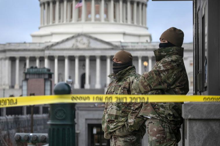 D.C. National Guard troops stand watch at the U.S. Capitol on Jan. 8 in Washington. Fencing was put up around the building the day before, following the storming of the Capitol by Trump supporters on Jan. 6.