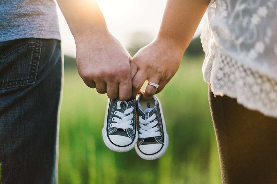 Adoptive parents hold infant shoes in anticipation of receiving their little one.