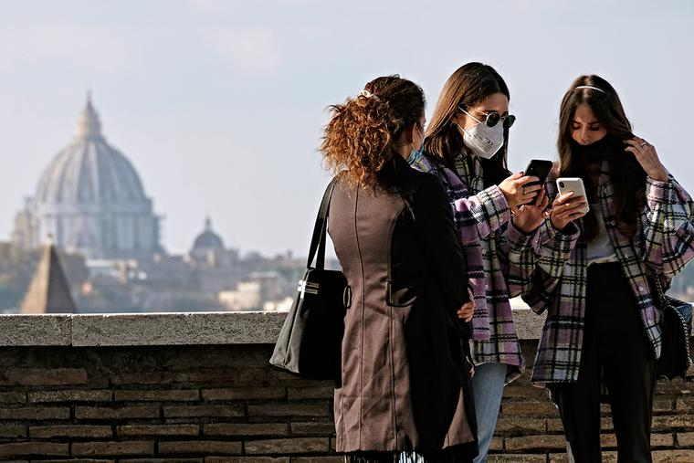 Women wearing protective masks look at their smartphone on a terrace of the Orange Garden (Giardino degli Aranci) on the Aventine Hill overlooking St. Peter's Basilica in Rome on Nov. 11, 2020.