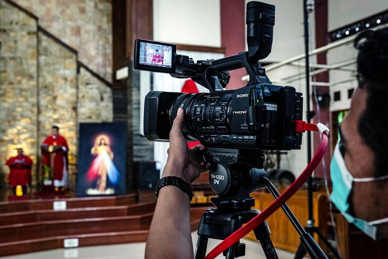 A broadcast crew holds a camera at a livestreamed Mass at the Paroki Kristus Raja Baciro Catholic church on April 10, 2020, in Yogyakarta, Indonesia.