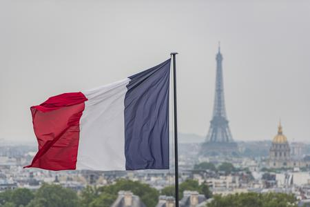 French flag waves above Paris with the Eiffel Tower in the background.