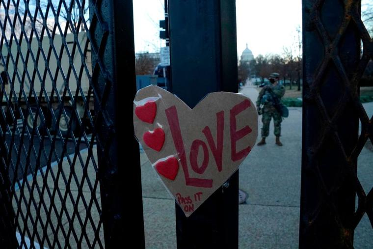 "A sign reading ""Love"" is placed on a barrier outside the US Capitol as National Guard troops stand guard ahead of the inauguration ceremonies for President-elect Joe Biden and Vice President-elect Kamala Harris on January 18, 2021 in Washington, DC."