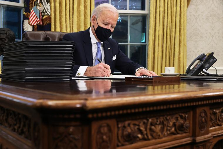 U.S. President Joe Biden prepares to sign a series of executive orders at the Resolute Desk in the Oval Office just hours after his inauguration today in Washington, D.C.