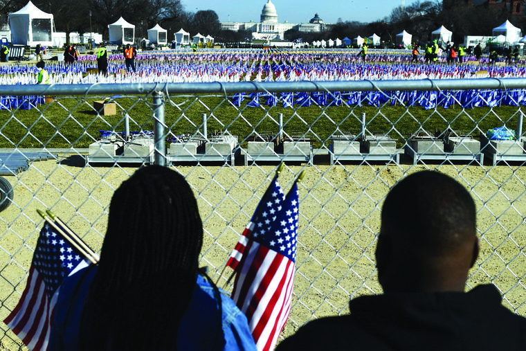 People collect flags that decorated the National Mall in Washington on Jan. 21, one day after the inauguration of U.S. President Joe Biden. The Presidential Inaugural Committee encouraged supporters to sponsor the flags through donations to 95 groups, including the Planned Parenthood Federation of America.