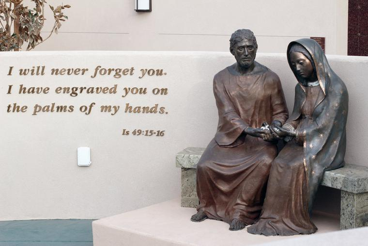 The memorial walls are centered around a life-size bronze statue of St. Joseph and Our Lady of Guadalupe, co-patrons of the unborn. Together they hold an unborn baby in their hands.