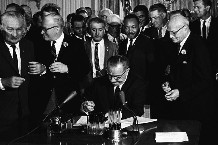 With Dr. Martin Luther King, Jr., looking on, President Lyndon B. Johnson signs into law the Civil Rights Act on July 2, 1964.