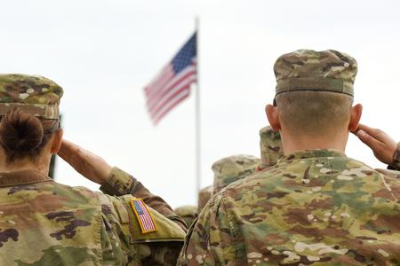 American soliders salute the American flag.