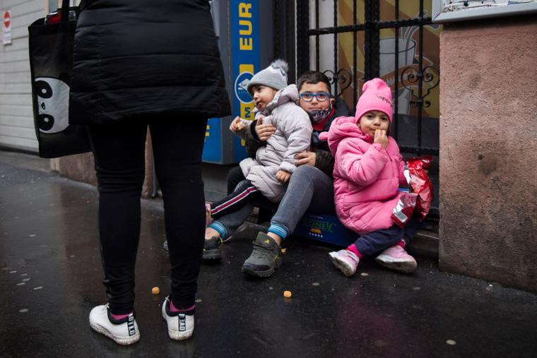 Children look on as people queue for food packages distributed by restaurant owner Norbert Bango (not pictured) in downtown Budapest on December 30, 2020. Hungarian families stricken by unemployment due to the Covid crisis who have fallen through the country's flimsy social security net have had to turn to a pop-up privately-run soup kitchen for help.