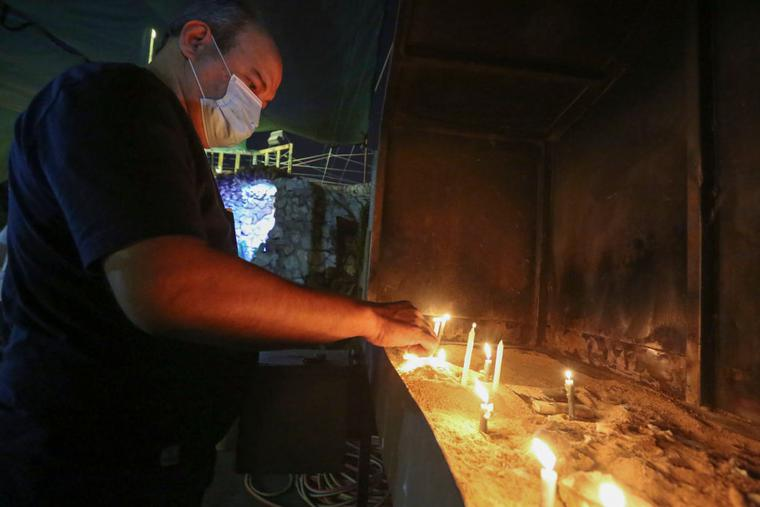 A worshipper lights a candle at the Chaldean Catholic Church of St. Joseph in the Iraqi capital Baghdad, on November 7, 2020. A few hundred thousand Christians are left in Iraq.
