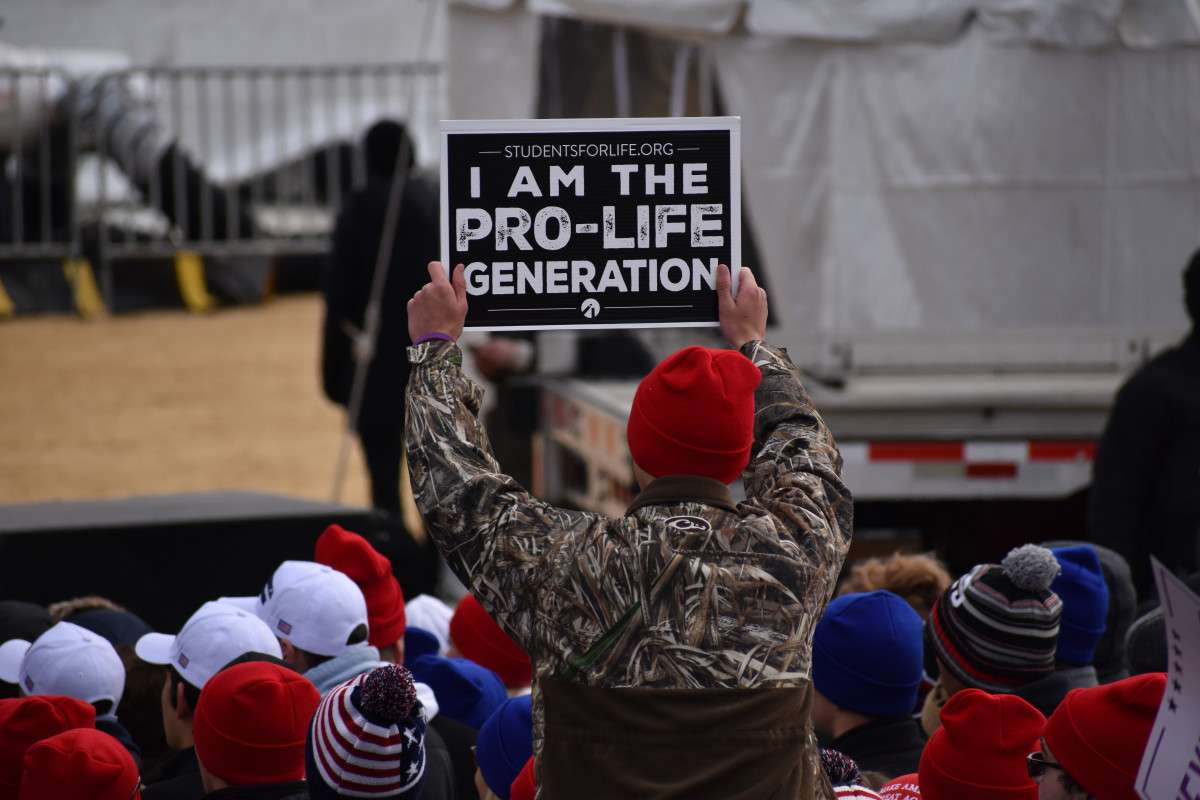 A man holds a pro-life sign at a rally.