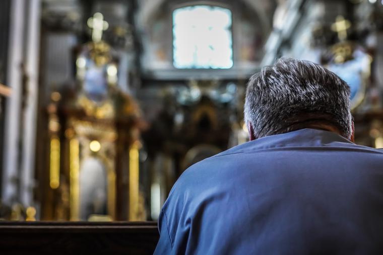A man sits alone inside a Catholic church praying.