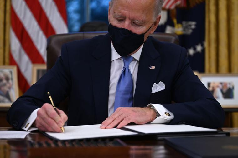 US President Joe Biden signs a series of orders in the Oval Office of the White House in Washington, DC, after being sworn in at the US Capitol on January 20, 2021.