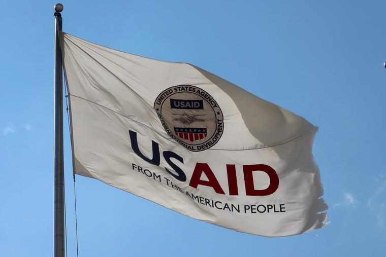 US AID Agency for International Development flag with emblem seal outside headquarters building.