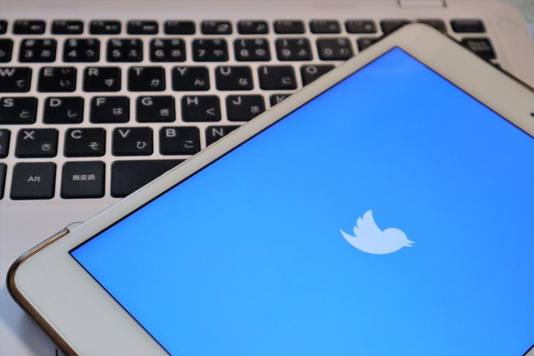 A smartphone showing the Twitter logo rests on a laptop.