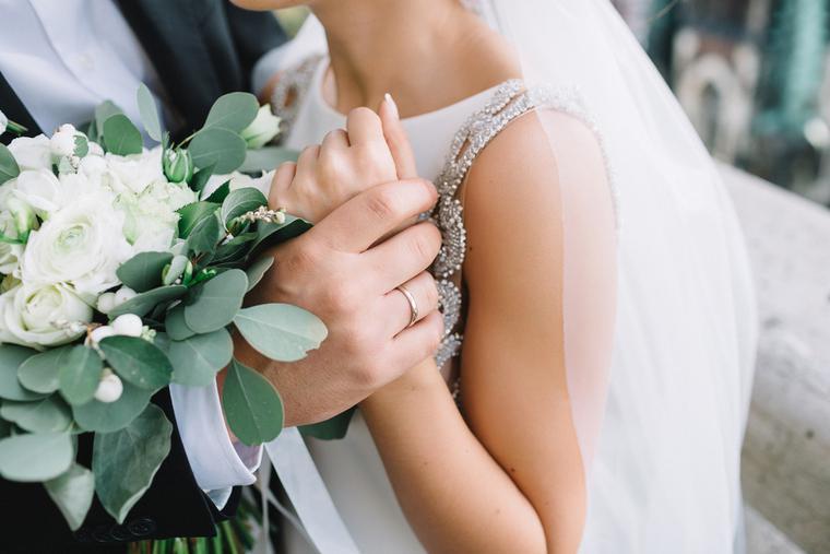 Groom holds bride's wrist on their wedding day.