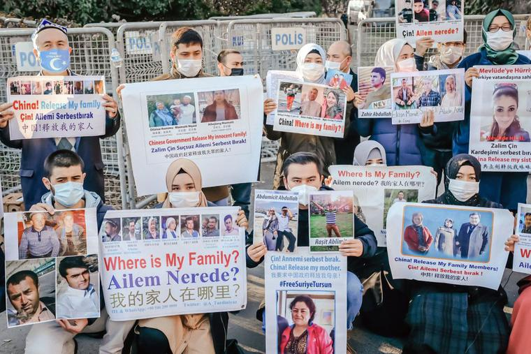 Members of the Muslim Uyghur minority hold placards as they demonstrate in front of the Chinese consulate on Dec. 30, 2020, in Istanbul, to ask for news of their relatives and to express their concern after China announced the ratification of an extradition treaty with Turkey.