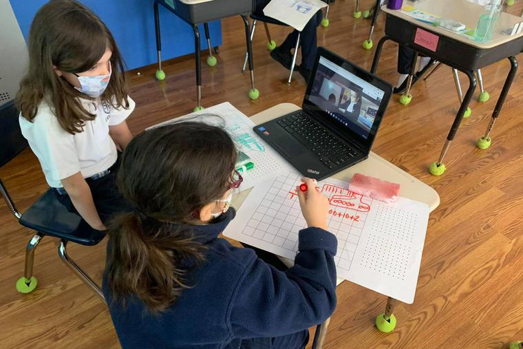 Students at St. Rita School in Webster, New York, make use of digital technology that connects in-person learners with their distance-learning peers.