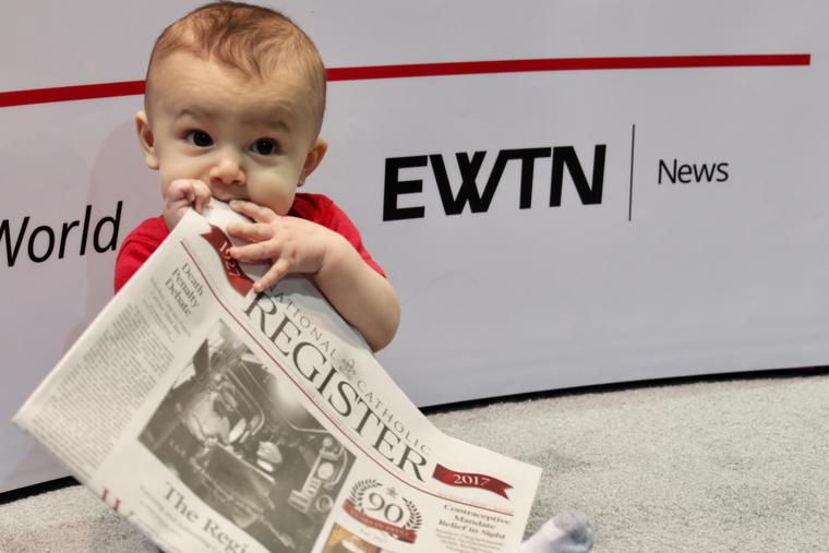 A young baby consuming every page of the National Catholic Register newspaper.