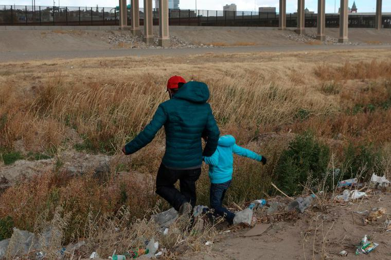 A Guatemalan migrant and his son cross the Rio Grande natural border between El Paso, state of Texas, US, and Ciudad Juarez, Chihuahua state, Mexico in search of political asylum on January 26, 2021.