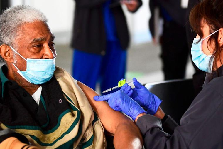 Elton Jackson, 80, looks on as he receives his COVID-19 vaccine, administered by Kathryne Acuna, director of Ambulatory Clinical Services at Kaiser Permanente, on Feb. 5, the opening day of a large-scale vaccination site at a parking structure at Cal Poly Pomona University in Pomona, California. The elderly are among those given priority during the vaccine rollout across the country.