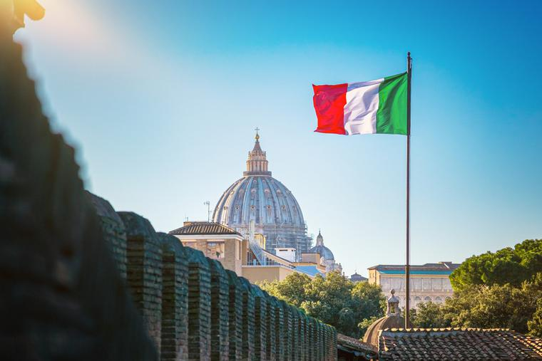View of Saint Peter Basilica with an Italian flag waving in the wind.