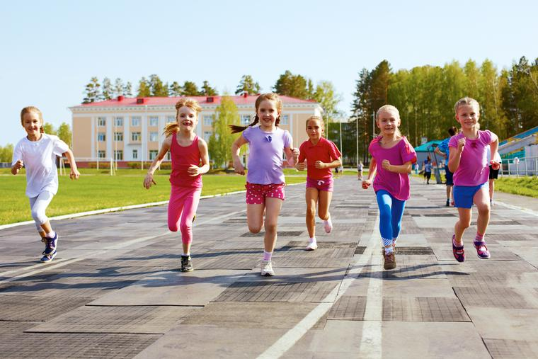 Young girls run outside on the track.
