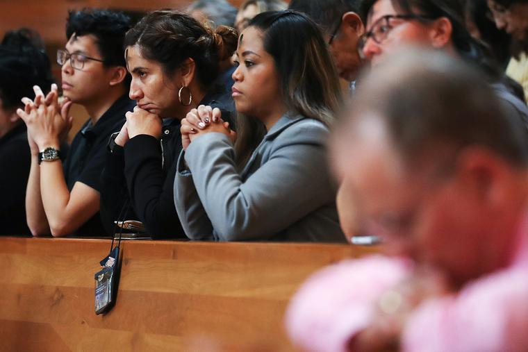 A family prays during Ash Wednesday Mass at the Cathedral of Our Lady of the Angels on Feb. 26, 2020, in Los Angeles, California.