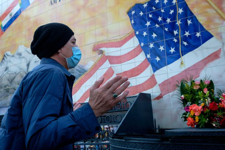 A man wearing a face mask prays in front of a mural outside Our Lady of Guadalupe Chapel in Los Angeles, Thursday, Nov. 26, 2020.