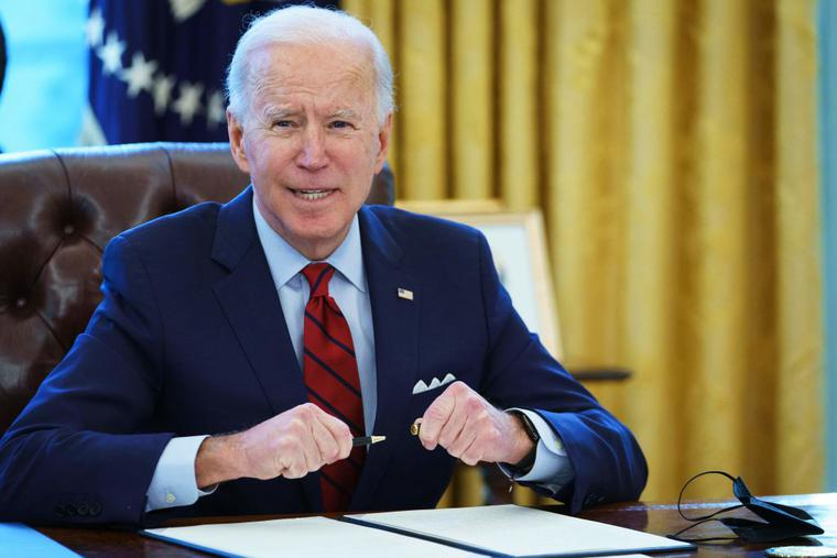US President Joe Biden prepares to sign executive orders in the Oval Office of the White House in Washington, DC, on January 28, 2021.