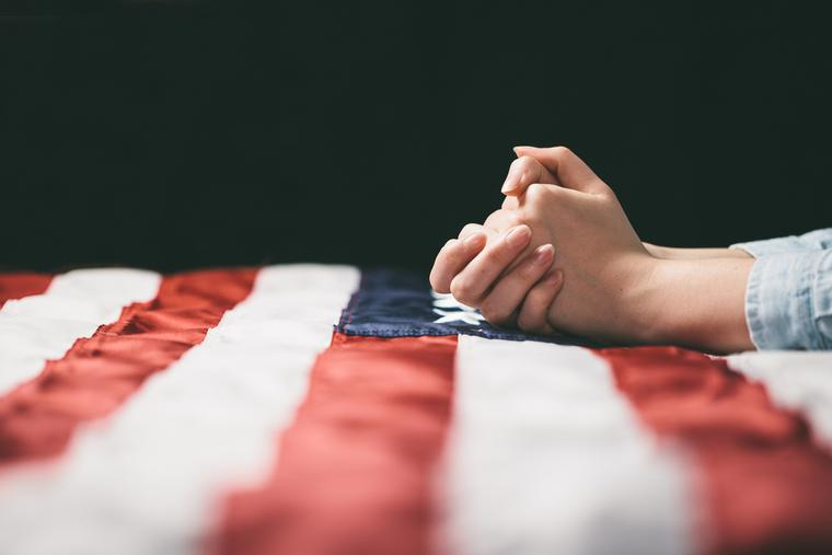 A woman prays over the American flag.