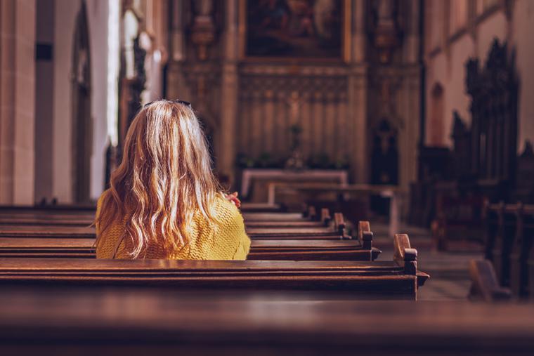 A woman sits alone inside a parish praying.