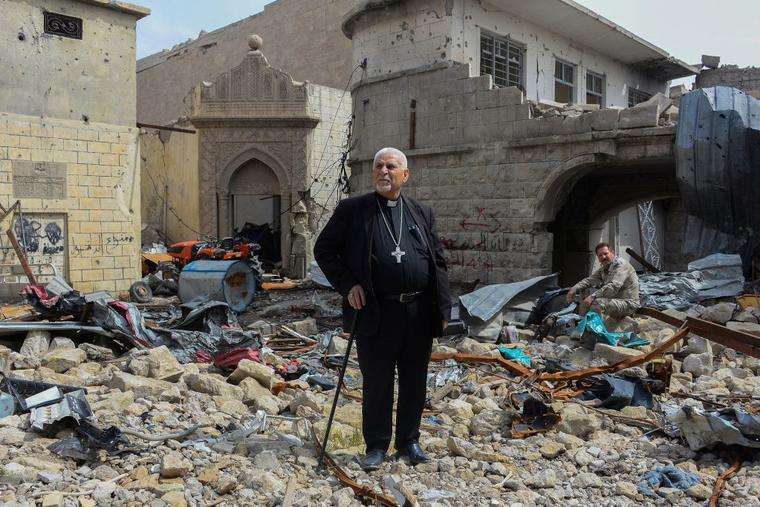 Father John Botros Moshi, the Syriac Catholic Archbishop of Mosul, Kirkuk, and the Kurdistan Region, stands in the rubbles of the Tahra church in Mosul on April 29, 2018. - The church, established during the seventh century, was destroyed by bombings when the regime was fighting jihadists in this area.