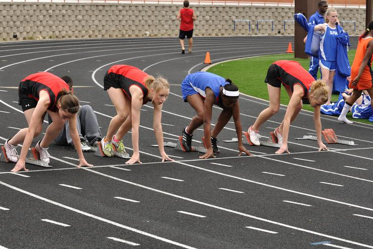 Teenage girls set to race in a track meet.