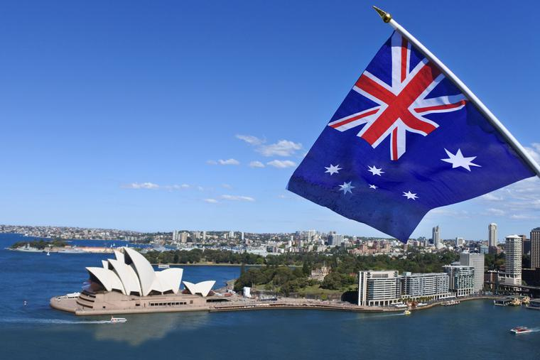 The National flag of Australia flies above the Sydney Harbor and the Opera house in Australia.