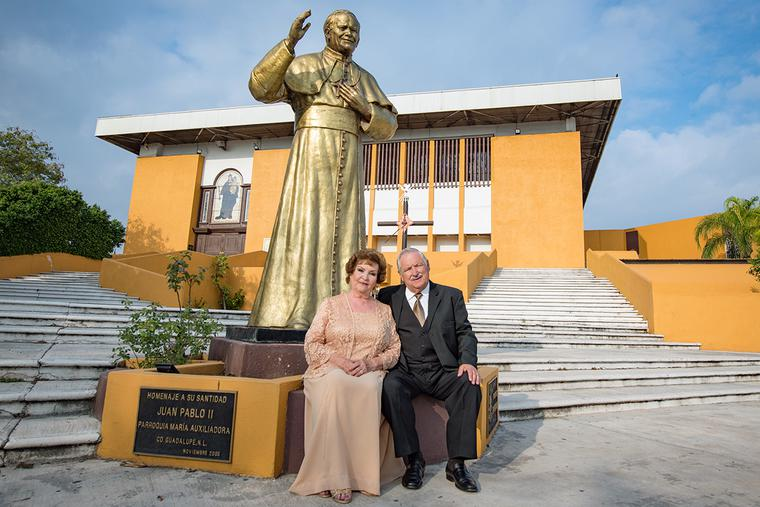 A couple sits together in front of a statue of Pope St. John Paul II at Maria Auxiliadora church in Monterrey, Mexico, on Jan. 18, 2020 — their 50th wedding anniversary.