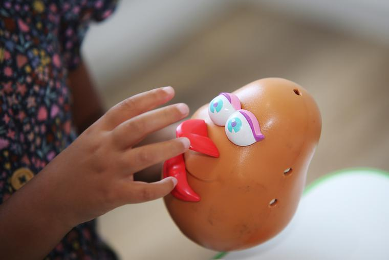 A young girl pieces together Hasbro's Mrs. Potato Head.